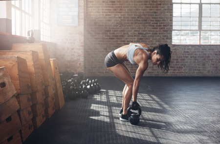 Photo for Full length shot of fitness woman doing crossfit exercising with kettle bell. Determined female model about to start her fitness regime at the crossfit gym. - Royalty Free Image