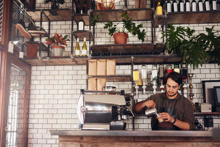 Foto de Indoor shot of young male barista making a cup of coffee while standing behind cafe counter. Young man pouring milk into a cup of coffee. - Imagen libre de derechos