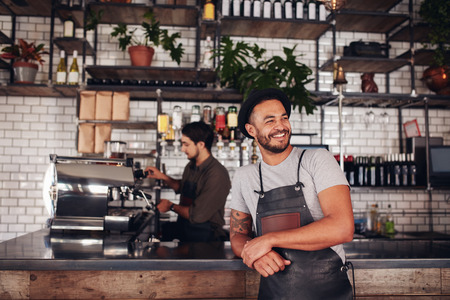 Foto de Portrait of cafe owner wearing a hat and apron standing at the counter and looking away. Barista working in background behind the counter making drinks. - Imagen libre de derechos
