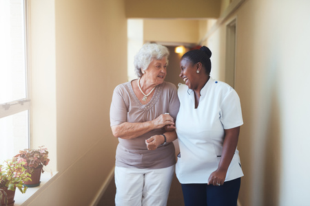 Foto de Portrait of happy female caregiver and senior woman walking together at home. Professional caregiver taking care of elderly woman. - Imagen libre de derechos