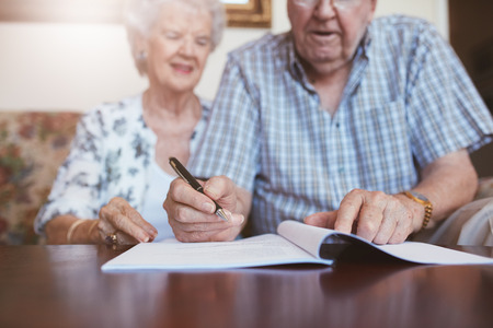 Foto de Senior couple signing will documents. Elderly caucasian man and woman sitting at home and signing some paperwork, focus on hands. - Imagen libre de derechos