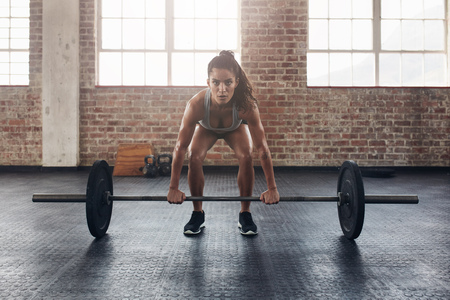 Photo pour Female performing deadlift exercise with weight bar. Confident young woman doing weight lifting workout at gym. - image libre de droit