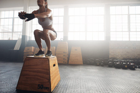 Foto de Shot of a young woman jumping onto a box as part of exercise routine. Fitness woman doing box jump workout at crossfit gym. - Imagen libre de derechos