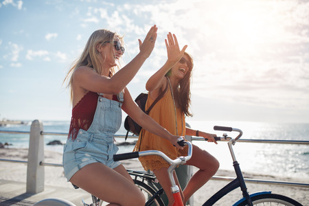 Photo for Female cycling on a summer day and giving each other a high five. Two young female friends riding their bicycles on the seaside promenade. - Royalty Free Image