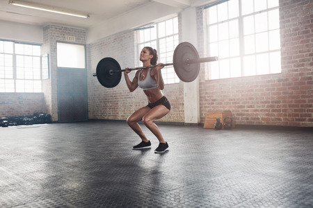 Photo pour Female bodybuilder doing exercise with a heavy weight bar in gym. Full length shot of fitness woman practicing weightlifting at health club. - image libre de droit