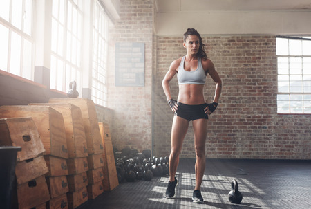 Photo for Full length shot of determined fitness woman walking in the crossfit gym. Muscular sportswoman warming up before a intense workout. - Royalty Free Image