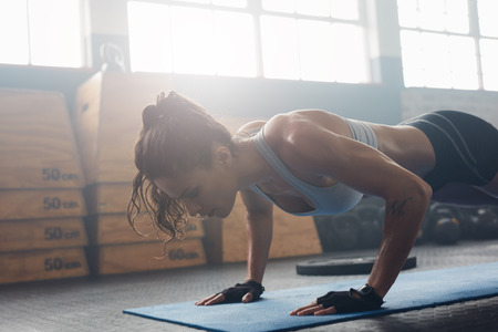 Photo for Shot of young woman doing push-ups at the gym. Muscular female doing pushups on exercise mat at gym. Female exercising on fitness mat at gym. - Royalty Free Image