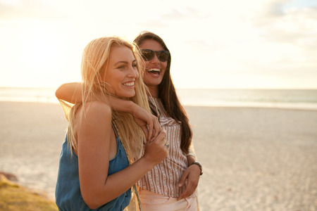 Photo for Two beautiful young women strolling on a beach. Female friends walking on the beach and laughing on a summer day, enjoying summer vacation. - Royalty Free Image