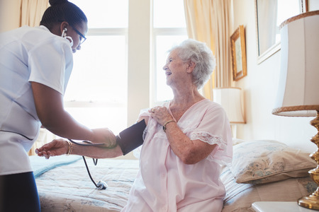 Photo for Nurse visiting senior female patient at home and taking blood pressure. Old woman sitting on bed. - Royalty Free Image