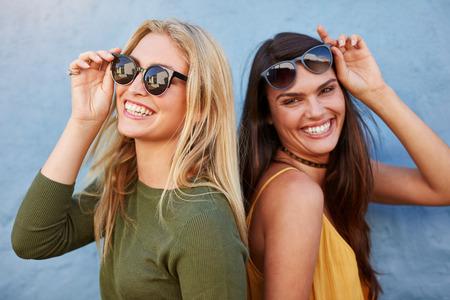 Photo for Pretty young female friends having fun. Both looking at camera and smiling against blue background. - Royalty Free Image