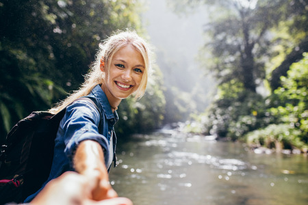 Photo pour Portrait of happy young woman holding hand of her boyfriend while walking by mountain stream. Couple enjoying a hike in nature. - image libre de droit