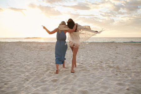 Photo pour Full length rear view shot of two woman friends walking together on the beach. Female friends taking a walk on the sea shore and having fun. - image libre de droit