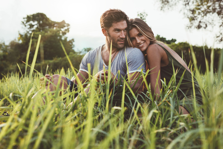 Foto de Shot of affectionate young couple enjoying a day outdoors. Man and woman sitting on grass field on a summer day. - Imagen libre de derechos