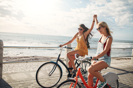Photo for Female friends enjoying cycling on a summer day. Two young female friends riding their bicycles on the seaside promenade. - Royalty Free Image