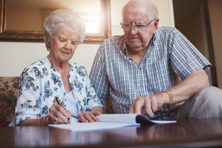 Photo pour Indoor shot of mature couple at home signing documents together. Senior man and woman sitting on sofa doing retirement paperwork. - image libre de droit