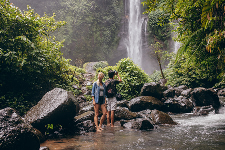 Foto de Young couple standing by the stream, with man taking photographs of waterfall. Couple of tourist enjoying in nature. - Imagen libre de derechos