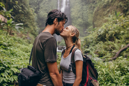 Photo pour Shot of loving young couple kissing while standing in the forest. Couple in love kissing near a waterfall in forest. - image libre de droit