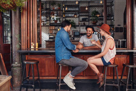 Photo pour Group of young friends sitting and talking at a cafe. Young men and women meeting in a coffee shop. - image libre de droit