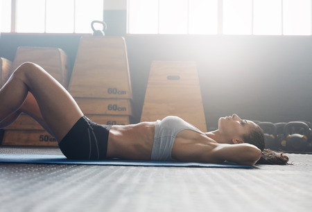 Photo for Side view image of fitness woman doing sit ups on an exercise mat. Muscular young woman lying on exercise mat with her hands behind head doing stomach exercises. - Royalty Free Image