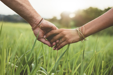 Photo for Shot of romantic couple holding hands in a field. Close up shot of man and woman with hand in hand walking through grass field. - Royalty Free Image