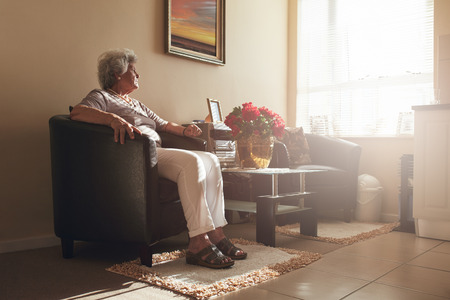 Photo pour Senior woman sitting alone on a chair at home. Retired woman relaxing in living room. - image libre de droit
