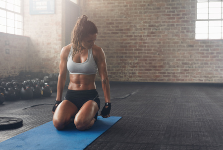 Photo for Shot of fitness woman sitting on exercise mat and looking at her triceps. Muscular woman working out at the fitness club. - Royalty Free Image