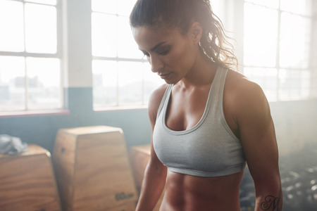 Photo pour Close up shot of muscular woman standing in the gym and looking down. She is wearing a sports bra. Female model taking a break from her training. - image libre de droit