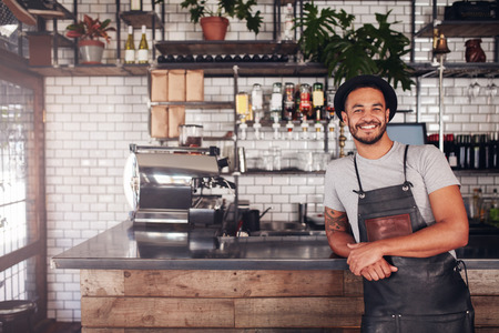 Foto de Portrait of young man standing at the counter in his cafe. Coffee shop working in apron and hat smiling at camera. - Imagen libre de derechos
