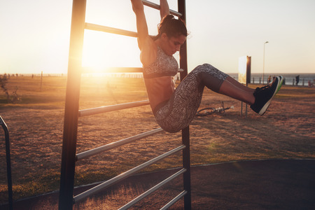 Photo for Candid shot of real healthy and fit woman performing hanging leg raises on outdoor fitness station in sunset at beach promenade. Showing strong abdominal six-pack. - Royalty Free Image