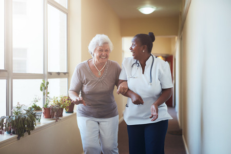 Photo pour Portrait of happy healthcare worker and senior woman walking together. Senior patient having fun with her home caregiver. - image libre de droit