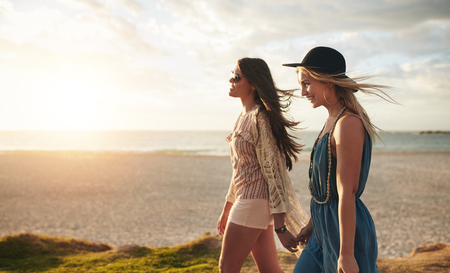 Beautiful young women strolling on a beach. Two friends walking on the beach on a summer day, enjoying vacation.