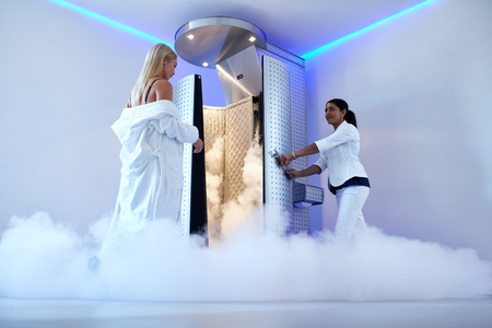 Foto de Full length woman entering freezing booth at the cosmetology clinic. Female taking cryotherapy treatment with beautician standing at the capsule door. - Imagen libre de derechos