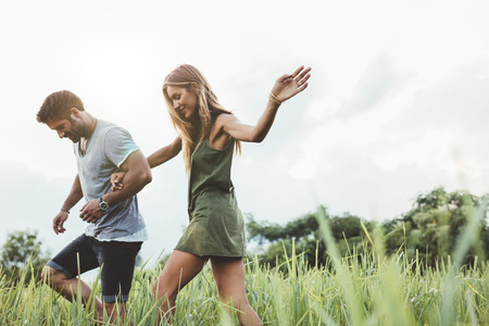Photo pour Outdoor shot of young couple walking through meadow hand in hand. Man and woman talking walk through grass field in countryside. - image libre de droit
