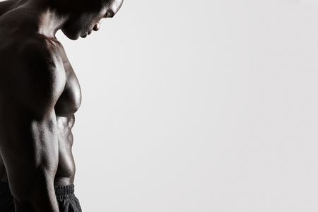 Photo for Side view cropped shot of young man with muscular body standing over grey background with lots of copy space. - Royalty Free Image