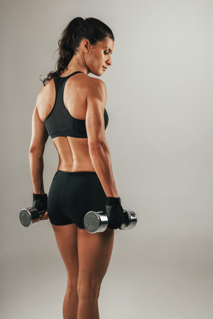 Foto de Three quarter view on back torso and thighs beautiful female athlete with pony tail and black outfit while holding dumbbells over gray background - Imagen libre de derechos