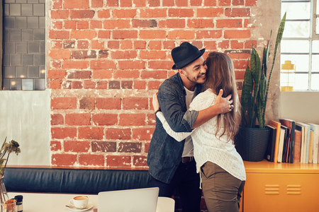 Foto de Portrait of young man greeting a woman at cafe. Young man hugging his girlfriend at a coffee shop. - Imagen libre de derechos