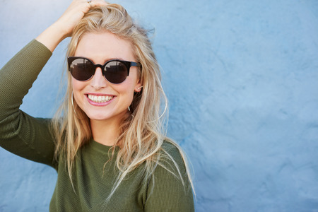 Photo pour Close up shot of pretty young woman in sunglasses smiling. Attractive young female model with copy space on blue background. - image libre de droit