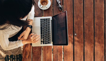 Foto de Overhead view of young woman working on her laptop at a cafe. Top view shot of female sitting at a table with a cup of coffee browsing internet. - Imagen libre de derechos
