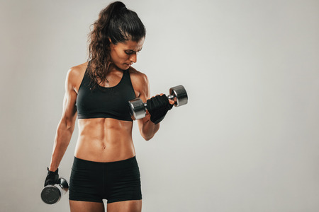 Photo pour Sweaty muscular woman with pony tail hair style and shorts curling dumbbell over gray background with copy space - image libre de droit