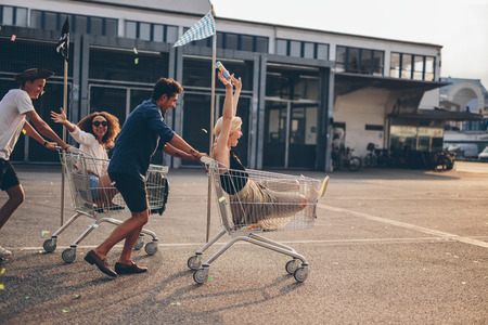 Foto de Young friends having fun on a shopping trolley. Multiethnic young people racing on shopping cart. - Imagen libre de derechos