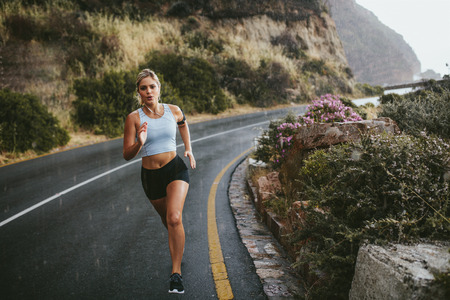Full length shot of young fitness woman running outdoors on an open highway in countryside. Determined female athlete sprinting on road during rain.