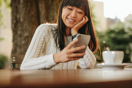 Photo for Happy young woman sitting at outdoor cafe and using her cellphone. Female model reading text message on smart phone at coffee shop  and smiling. - Royalty Free Image