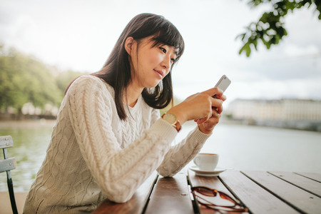 Photo for Shot of beautiful asian woman using mobile phone at cafe. Young female sitting at coffee table outdoors using smartphone. - Royalty Free Image