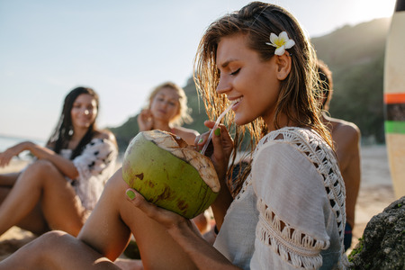 Photo pour Side portrait of attractive young woman drinking coconut juice with her friends sitting in background. Young people relaxing on the beach on summer vacation. - image libre de droit