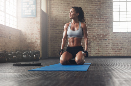 Foto de Indoor shot of  muscular young woman exercising at gym. Fitness model in sportswear sitting on exercise mat and looking away. - Imagen libre de derechos