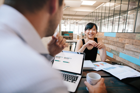 Foto de Shot of two business colleagues discussing work in office. Smiling young asian woman meeting with office manager. - Imagen libre de derechos