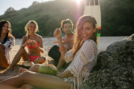 Photo pour Excited young woman having fun on the beach with her friends in background. Group of friends enjoying summer holidays on the beach. - image libre de droit
