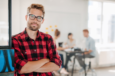 Photo pour Portrait of a positive looking young business professional standing with his arms crossed with coworkers talking in the background. - image libre de droit