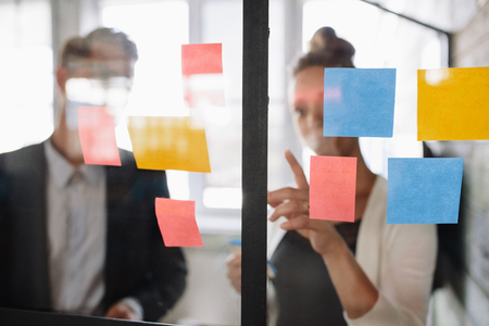 Foto de Two business colleagues working on project together. Business woman pointing at sticky note to male colleague on glass wall in office. - Imagen libre de derechos