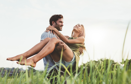 Photo for Young man carrying his girlfriend through a grass field. Couple on holiday in nature having fun. - Royalty Free Image